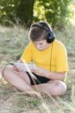 Muchacho en los auriculares que miran la tableta en Fotos de archivo