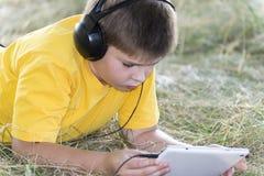 Muchacho en los auriculares que miran la tableta en Imagen de archivo
