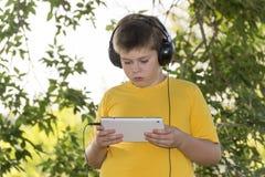 Muchacho en los auriculares que miran la tableta en Fotografía de archivo libre de regalías