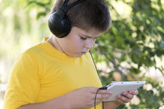 Muchacho en los auriculares que miran la tableta en Imágenes de archivo libres de regalías