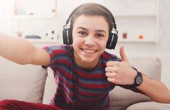 Muchacho en los auriculares que toman el selfie, como gesto Imagenes de archivo