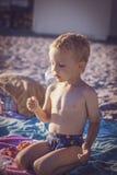 Muchacho en los pantalones cortos que se sientan en la playa y que comen cerezas Fotos de archivo libres de regalías