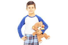 Muchacho en los pijamas que sostienen el oso de peluche Fotos de archivo
