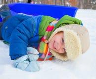 Muchacho en los trineos en nieve Fotos de archivo libres de regalías