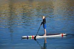 Muchacho en paddleboard en Dana Point Harbor, California Imagen de archivo