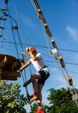 Muchacho en parque de la aventura del bosque Niño en casco anaranjado y subidas blancas de la camiseta en alto rastro de la cuerd imagenes de archivo