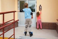 Muchacho en pcteres de ruedas y muchacha delante de la casa Fotos de archivo libres de regalías