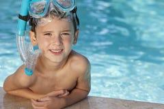 Muchacho en piscina con los anteojos y el tubo respirador azules Fotos de archivo libres de regalías