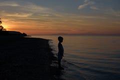 Muchacho en puesta del sol fotografía de archivo libre de regalías