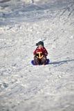 Muchacho en rojo en un trineo Foto de archivo libre de regalías