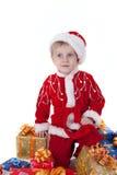 Muchacho en ropa de la Navidad con los juguetes Imagen de archivo