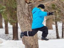 Muchacho en saltos del parque del invierno en la nieve acumulada por la ventisca foto de archivo