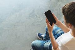 Muchacho en sentarse blanco de la camiseta y de las gafas de sol interior y smartphone de las aplicaciones El adolescente juega a Imágenes de archivo libres de regalías
