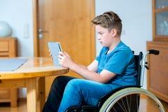 Muchacho en silla de ruedas usando la PC de la tableta Foto de archivo