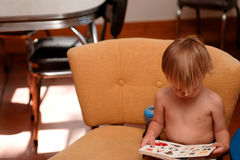 Muchacho en silla que lee un libro Fotos de archivo libres de regalías
