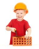 Muchacho en sombrero duro con la paleta y ladrillo aislado imagen de archivo libre de regalías