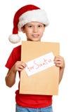 Muchacho en sombrero rojo con la letra a santa - concepto de la Navidad de las vacaciones de invierno Foto de archivo libre de regalías