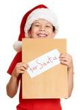 Muchacho en sombrero rojo con la letra a santa - concepto de la Navidad de las vacaciones de invierno Imagen de archivo libre de regalías