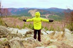 Muchacho en soporte caliente amarillo de la chaqueta en una roca en un día de primavera ventoso frío Forma de vida activa, activi Imágenes de archivo libres de regalías