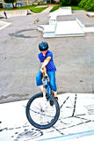 Muchacho en su bici en el parque del patín Imágenes de archivo libres de regalías