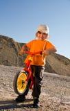 Muchacho en su bici roja del balance Foto de archivo libre de regalías