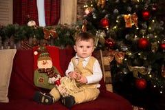 Muchacho en traje beige con la actual sentada al lado de un árbol de navidad Imagen de archivo