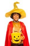 Muchacho en traje del mago con el cubo de Halloween del caramelo Fotos de archivo libres de regalías