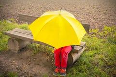 Muchacho en un banco ocultado por un paraguas amarillo Fotografía de archivo