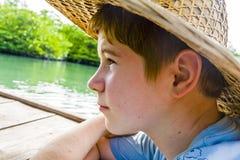 Muchacho en un barco con el sombrero de paja adentro en Imagenes de archivo