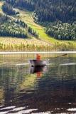 Muchacho en un barco de rowing en un lago de la montaña Foto de archivo libre de regalías