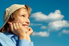 Muchacho en un casquillo bajo un cielo azul Foto de archivo