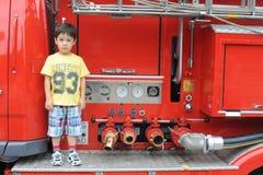 Muchacho en un coche de bomberos Fotos de archivo libres de regalías