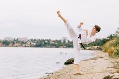 Muchacho en un kimono blanco con la correa marrón en un fondo natural Concepto intenso del ejercicio del karate Copie el espacio Foto de archivo