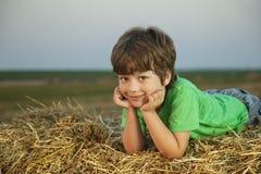 Muchacho en un pajar en el campo Foto de archivo libre de regalías