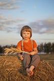 Muchacho en un pajar en el campo Fotografía de archivo libre de regalías