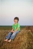 Muchacho en un pajar en el campo Fotografía de archivo