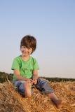 Muchacho en un pajar en el campo Imágenes de archivo libres de regalías