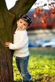 Muchacho en un parque, colocándose al lado de un árbol Fotos de archivo libres de regalías