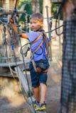 Muchacho en un parque de la aventura que sube Imagen de archivo