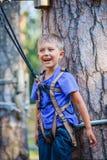 Muchacho en un parque de la aventura que sube Foto de archivo