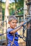 Muchacho en un parque de la aventura que sube Imagenes de archivo