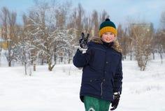 muchacho en un sombrero con un bubón afuera en invierno foto de archivo