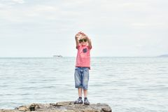 Muchacho en un sombrero y una camiseta rayada que defienden en una roca el mar Imágenes de archivo libres de regalías