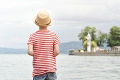 Muchacho en un sombrero y una camiseta rayada que se colocan en la playa Visión desde la parte posterior Imagen de archivo libre de regalías