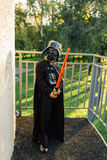 Muchacho en un traje de Darth Vader con la espada Imagen de archivo