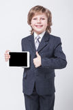 Muchacho en un traje de negocios y un lazo que sostienen una tableta Fotos de archivo libres de regalías