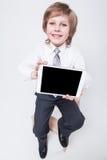 Muchacho en un traje de negocios y un lazo que sostienen una tableta Fotografía de archivo libre de regalías