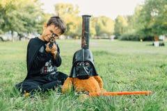 Muchacho en un traje del oso de Darth Vader y de peluche en una máscara de Darth Vader con la espada Imagen de archivo