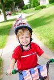 Muchacho en una bici el 4 de julio Imágenes de archivo libres de regalías