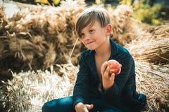 Muchacho en una brisa en un pueblo del otoño Niños del otoño con humor otoñal Tiempo del otoño para los niños en granja Forma de  imagen de archivo